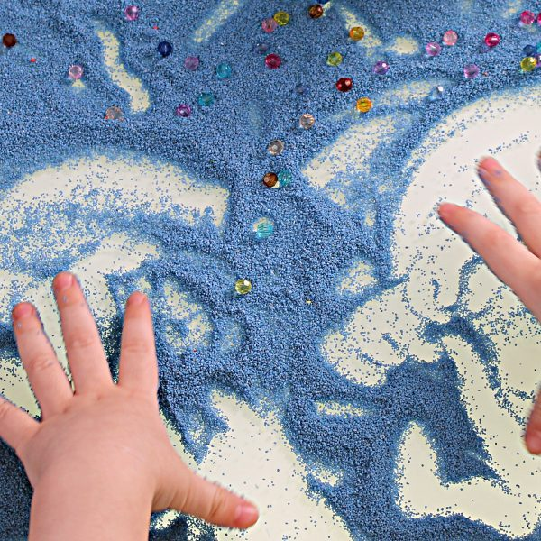 sand therapy,  child's hands are painted on a white table with blue sand
